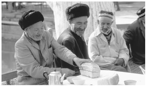 A man cuts bread in a choyhana, or tea house. The tea house is the central gathering place for Uzbek men.