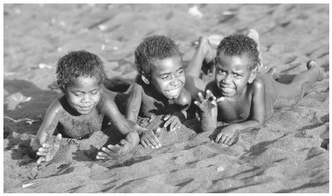 Children from the Jon Frum Cargo Cult Village play in the black sand beach on Tanna Island, which is a short distance from the active volcano Yasur. Vanuatu is a mostly volcanic archipelago of over eighty islands.