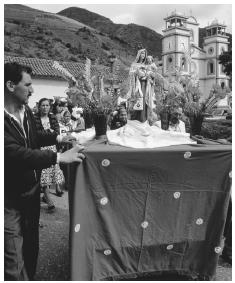 Parishioners push a portable shrine past a church during a festival. Most Venezuelans practice Catholicism.