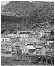 A pile of slate rests above a Welsh town. Mining is an important industry in Wales.