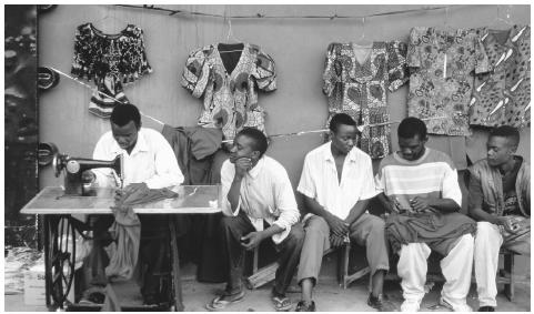 A tailor's stall market in Lusaka, Zambia. The stall is not only the tailor's business, but it is also a place to socialize.