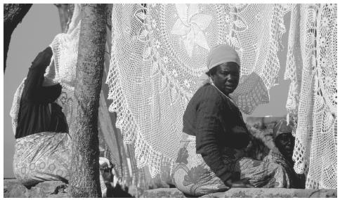A woman selling crocheted tablecloths in Harare. Many enterprises  in the informal sector are based on women's traditional activities.