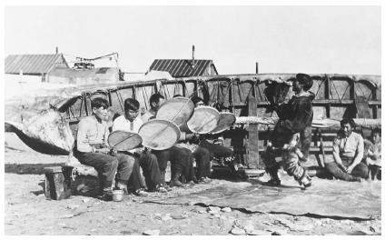 Inuit Men In Nome Alaska Play Drums And Sing As Another Man Dances