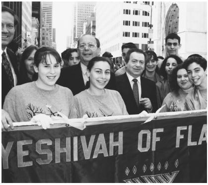 U. S. Senator Alfonse D'Amato (left center), comedian Jackie Mason (center), and others celebrate the annual Salute to Israel Parade in New York City.