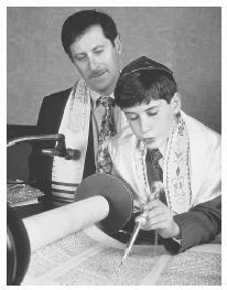 This boy reads from the Torah during his Bar Mitzvah.